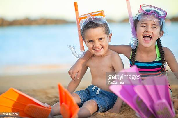 Young boy and girl on tropical beach going snorkeling