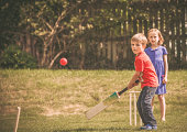 Young boy and girl play cricket