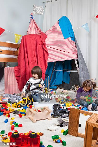 A young boy and girl playing in a bedroom