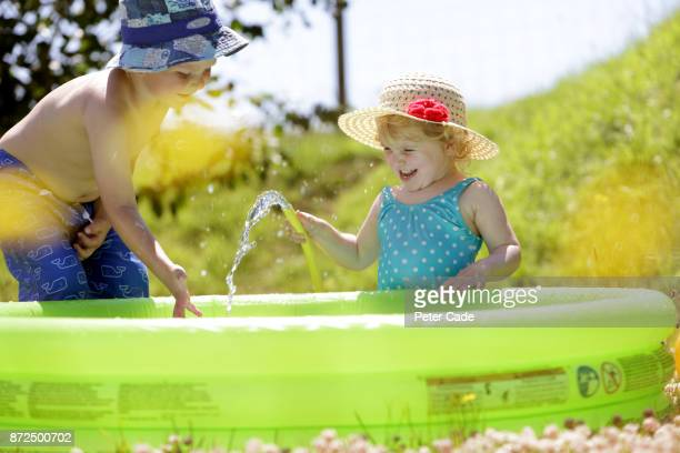 Young boy and girl playing in paddling pool in gardden