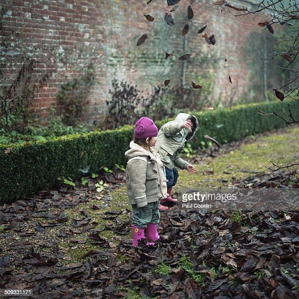Young boy and girl playing with winter leaves