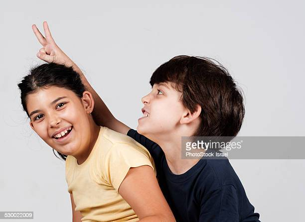 Young boy and girl playing, young boy holding up fingers as rabbit ears