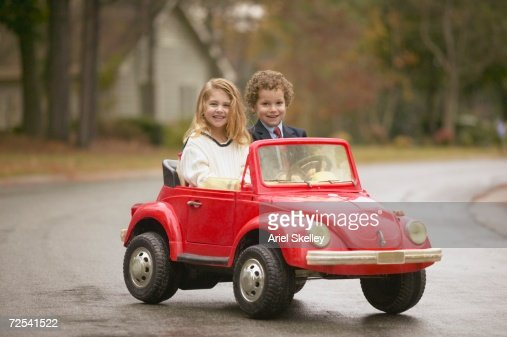For Boys Toy Cars To Ride In : Young boy and girl riding in toy car stock photo getty