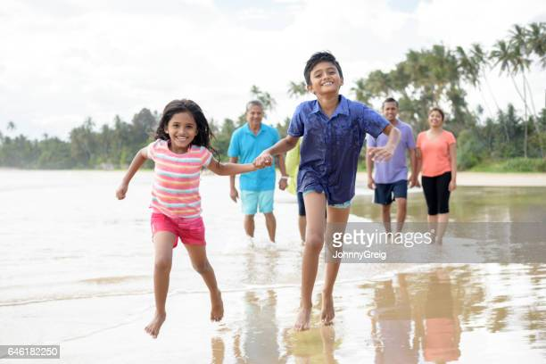 Young boy and girl running on beach holding hands