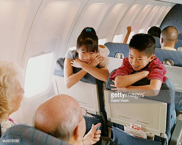 Young Boy and Girl Sit on a Plane, Talking to a Senior Couple Behind Them