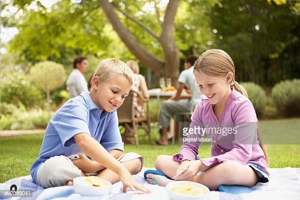 Young Boy and Girl Sit on a Rug in Their Garden Playing a Game of Cards