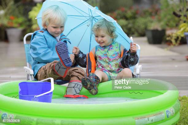 Young boy and girl sitting next to paddling pool outside in the rain under umbrella