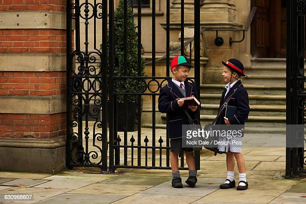 Young boy and girl students in uniform talking outside the school
