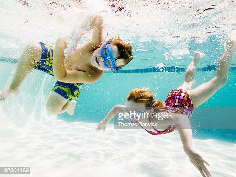 Young Boy And Girl Swimming Underwater In Pool Stock Photo Getty Images
