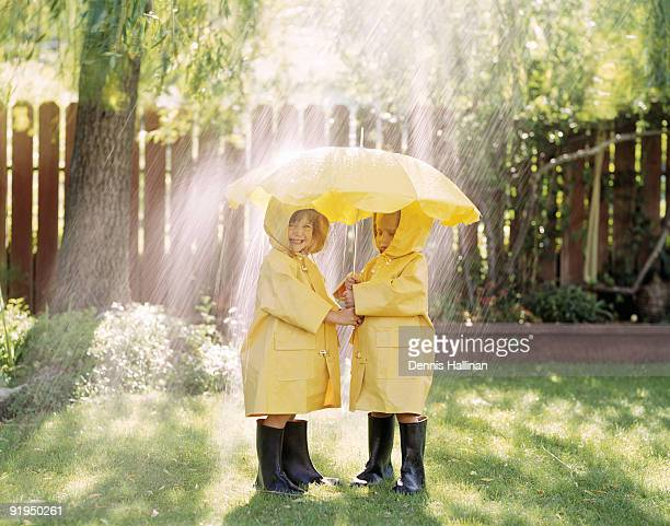 Young boy and girl under umbrella in rain