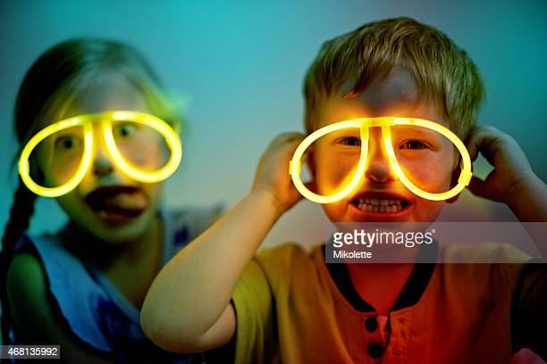 Young boy and girl wearing glow stick glasses at night