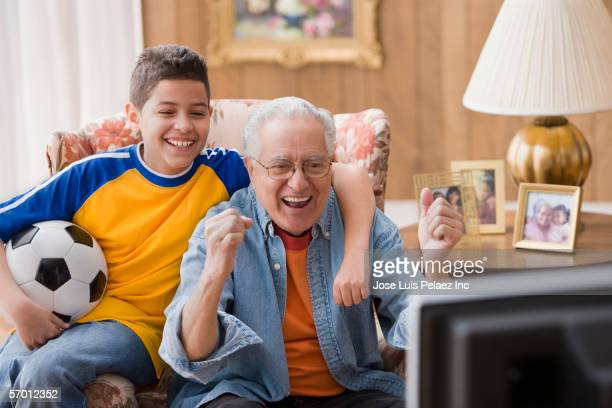 Young boy and his grandfather watching sports