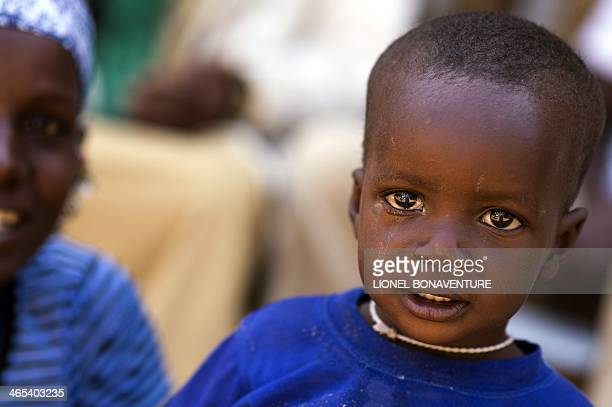 A young boy and his mother wait to see ophthalmologist on January 25 2014 in Leo Burkina Faso The French cosmetics company L'Occitane has been...