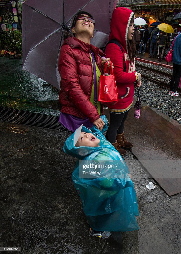 A young boy and his mother watch as thier lantern floats away at the Pingxi Sky Lantern Festival on February 14, 2016 in Pingxi District, New Taipei City, Taiwan. The event is the second of three organised lantern releases and the theme for the launch is 'Two Hearts Together'. Participants were encouraged to 'leave their love in Pingxi' and draw hearts on their lanterns.