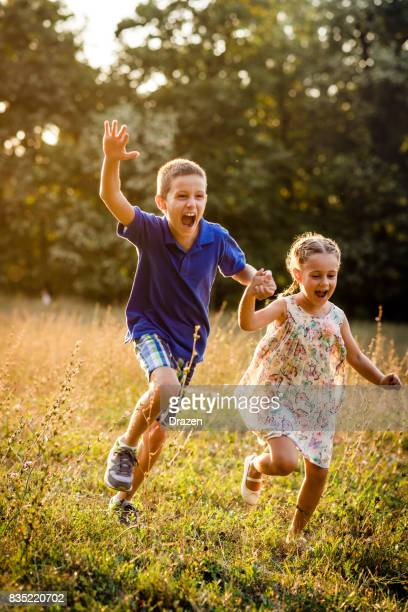 Young boy and his sister chasing each other