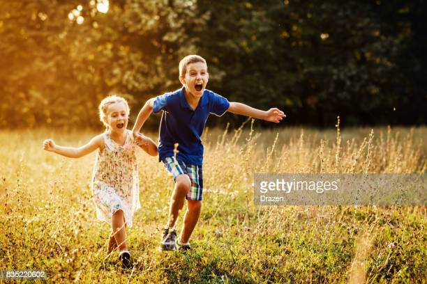 Young boy and his sister running in park