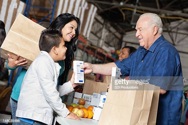 Young boy and mother donating food at a pantry