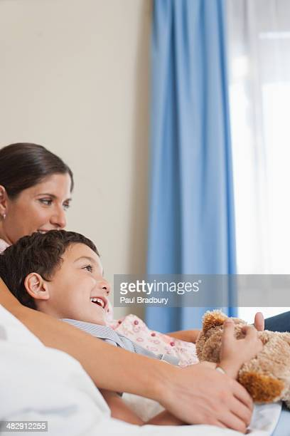 Young boy and woman in hospital bed with teddy bear