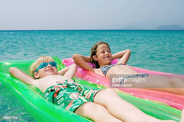 Young boy and young girl floating on inflatable rafts in the water smiling.
