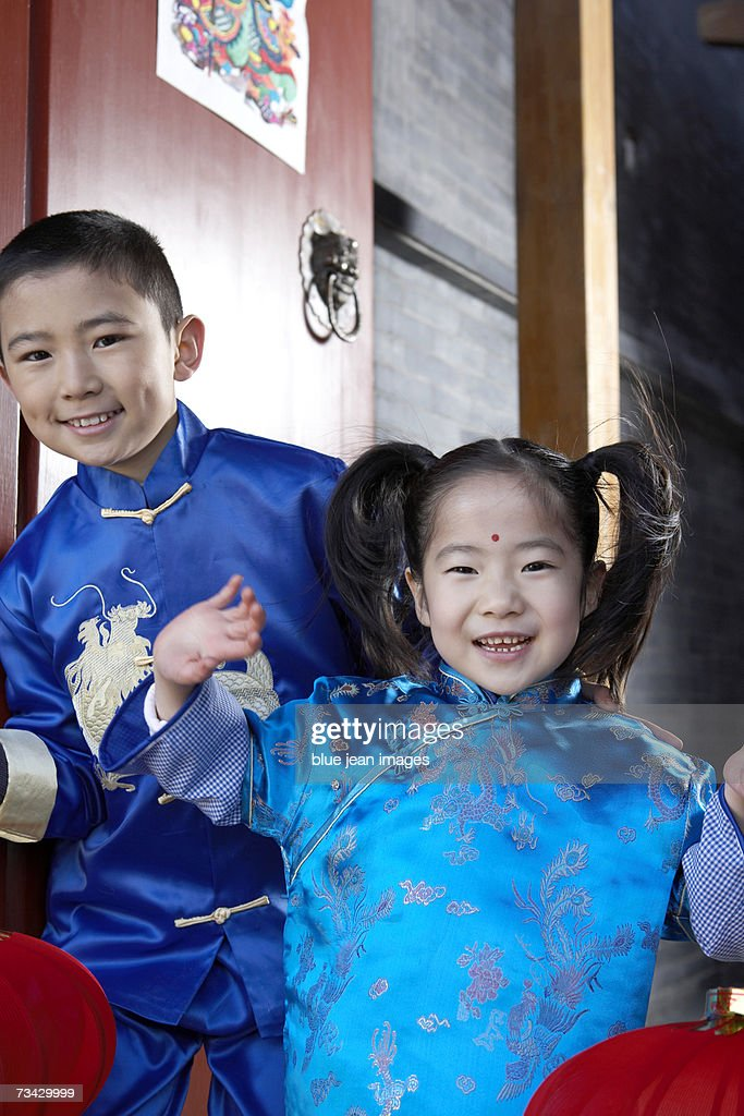 A young boy and young girl holding lanterns, wave as they stand in the open doorway of their traditional courtyard home decorated for the Chinese New Year. : Stock Photo