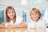 Young boy and young girl in kitchen with glasses of milk