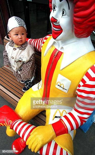 A young boy approaches a lifesize Ronald McDonald statue with caution 27 March in Beijing which now has over 30 of the US hamburger franchises Once a...