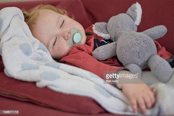Young boy asleep sucking pacifier