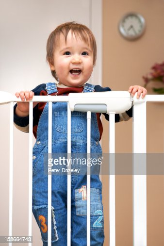 Young boy at a stair gate : Stock Photo