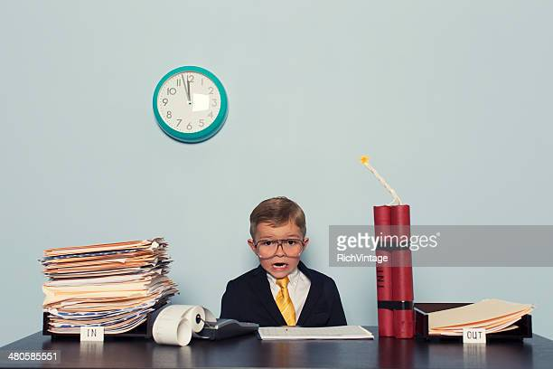 Young Boy at Business Desk Awaits Deadline