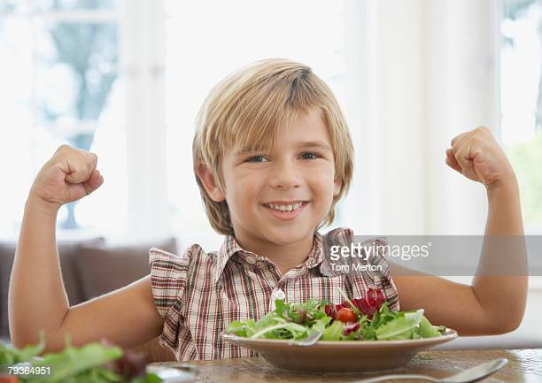 Young boy at dining room table flexing