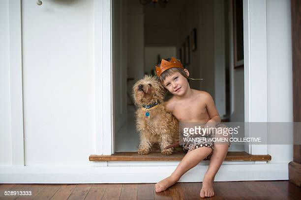 Young boy at home cuddling dog, sword, kings crown