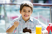 Young boy at restaurant eating dessert and smiling (selective focus)