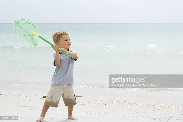 Young boy at the beach, holding up net to catch ball