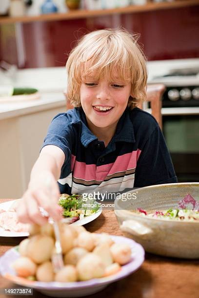 Young boy at the family dinner table helping himself to potatoes