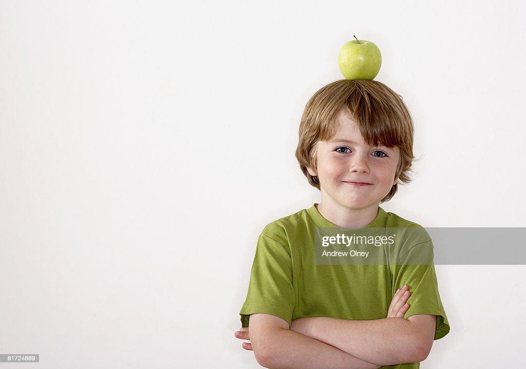 Young boy balancing apple on his head : Stock Photo