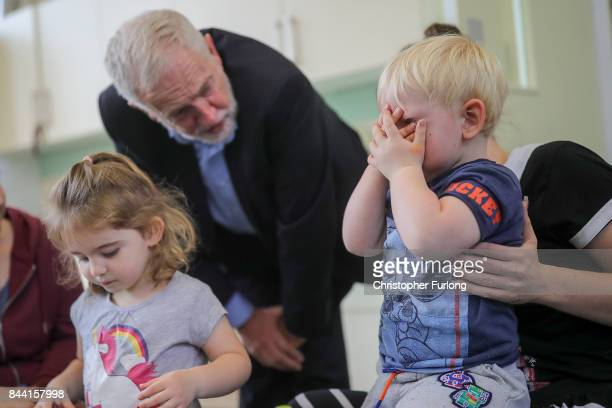A young boy becomes camera shy as Labour Party Leader Jeremy Corbyn talks to children and staff during a visit to the Pen Green Centre on September 8...