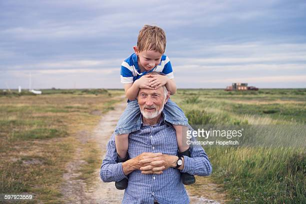 Young boy being carried by his grandad