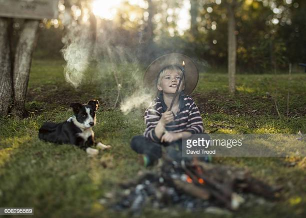 Young boy beside camp fire.