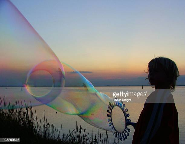 Young boy blows a worm like bubble as the sun sets
