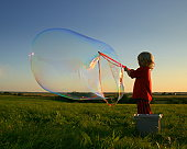 Young boy blows large soap bubble