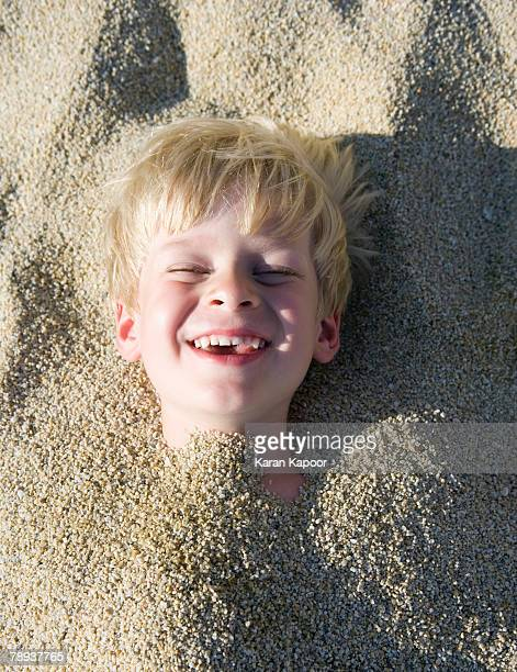 Young boy buried in the sand laughing.