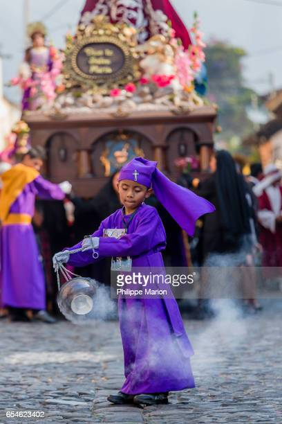 Young boy burning incense in front of religious float (anda)