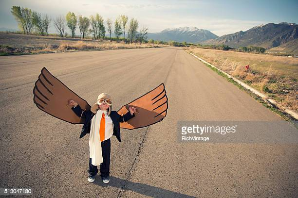 Young Boy Businessman Dressed in Suit with Cardboard Wings