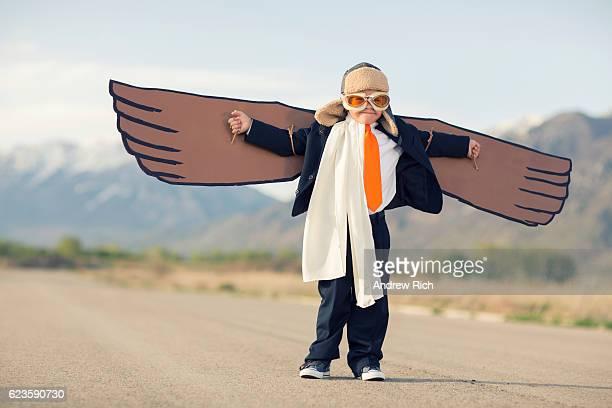 Jeune garçon habillé en costume homme d'affaires avec le carton ailes de