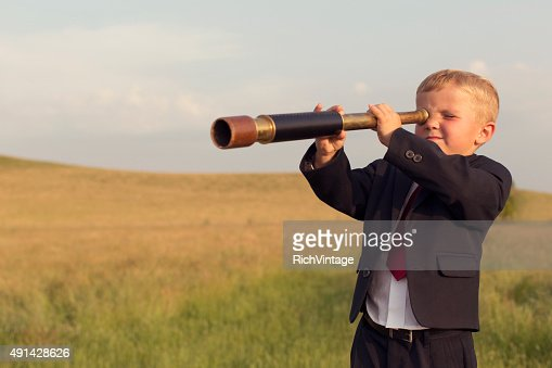 Young Boy Businessman Looking through Telescope