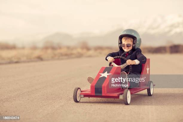 Young Boy Businessman Races Toy Car on Blacktop