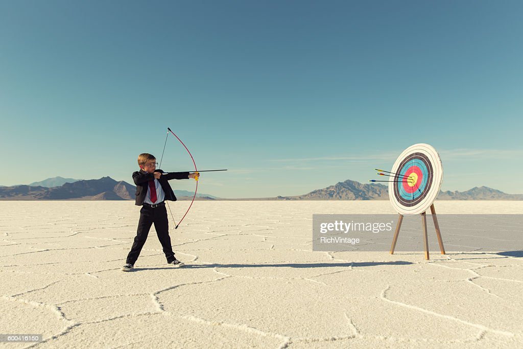 Young Boy Businessman Shoots Arrows at Target : Stock Photo