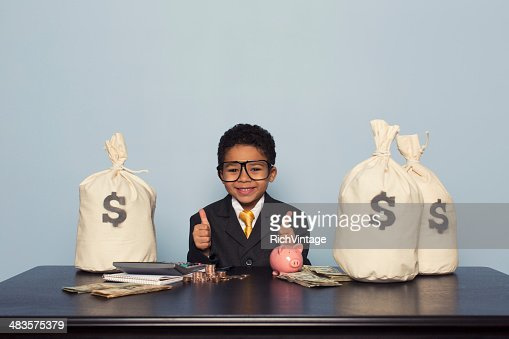 Young Boy Businessman Sits with U.S. Money Savings