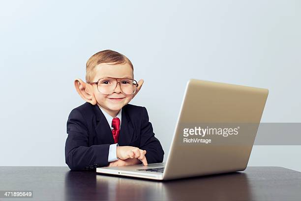 Young Boy Businessman Wears Large Ears at Laptop