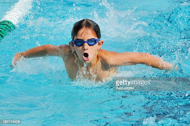 Young Boy Butterfly Stroke Swimmer Racing in Pool